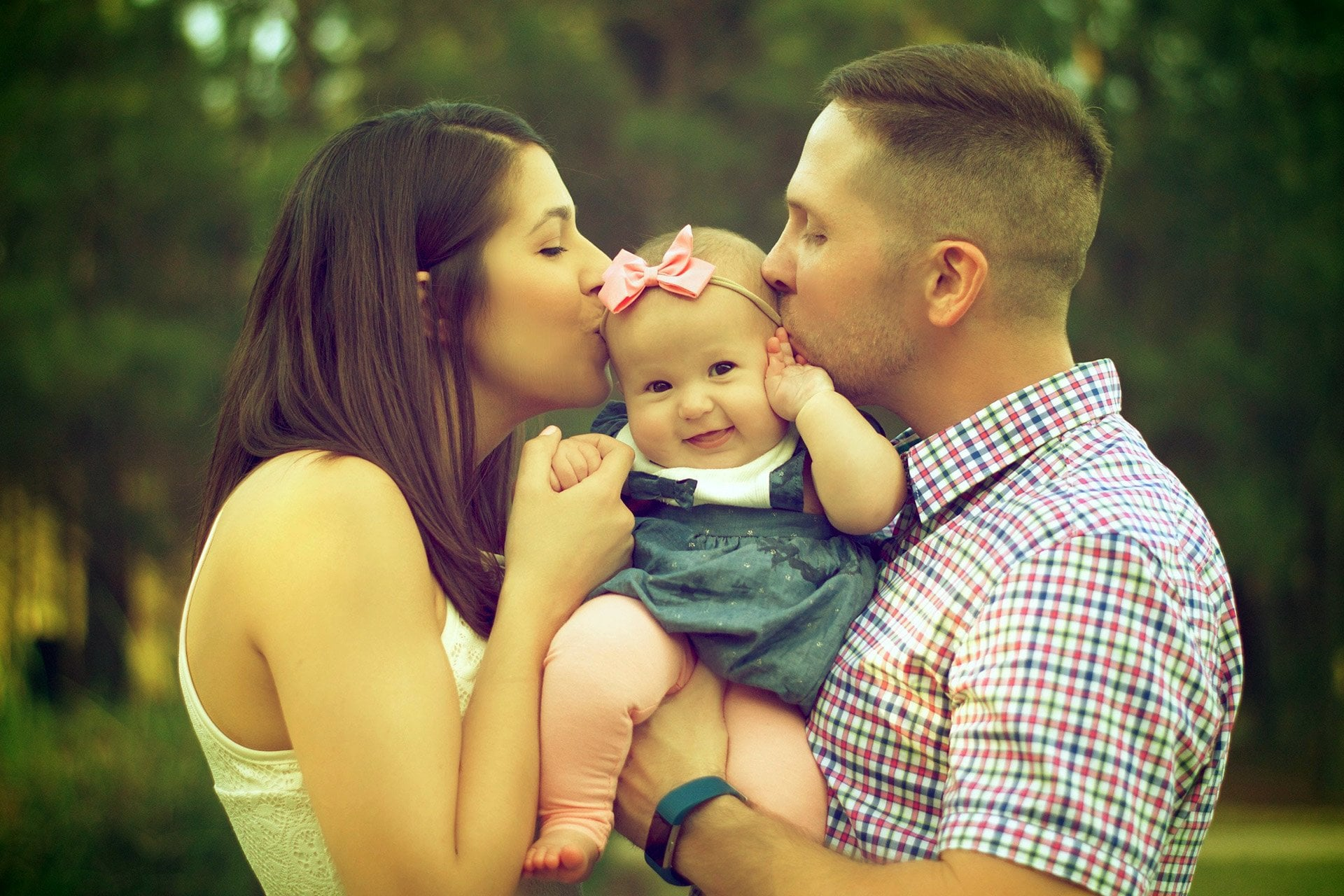 parents kissing toddler in the woods